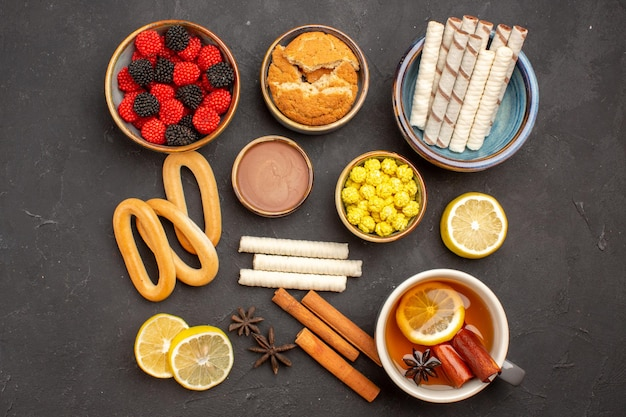 Cukierki konfiturowe z widokiem z góry z filiżanką herbaty i ciasteczkami na ciemnej powierzchni herbata herbatniki ze słodkich cukierków