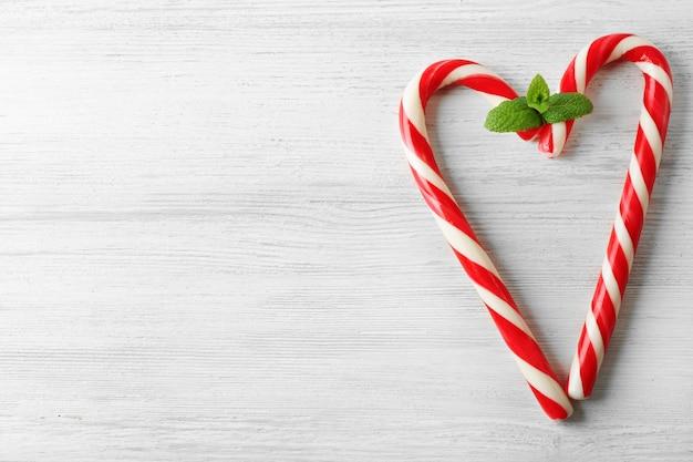 Cukierki lollipop jak serce z miętą na jasnym tle