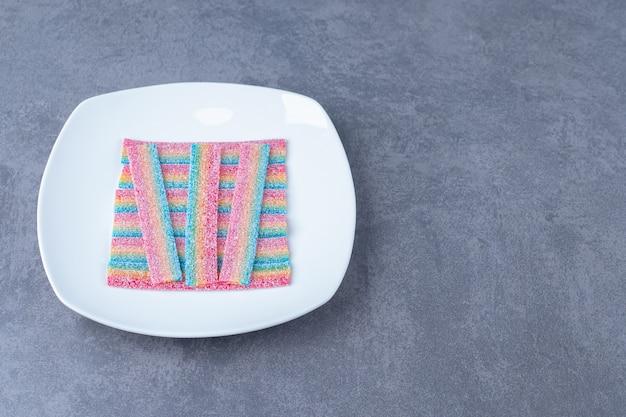 Cukierki lukrecja na talerzu na marmurowym stole.