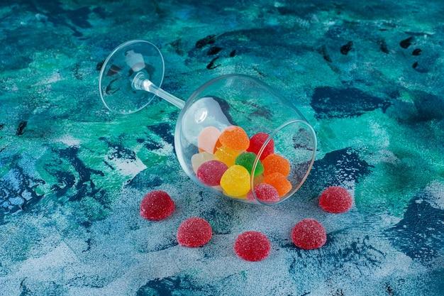 Cukierki marmoladowe w przewróconym szkle, na niebieskim tle.