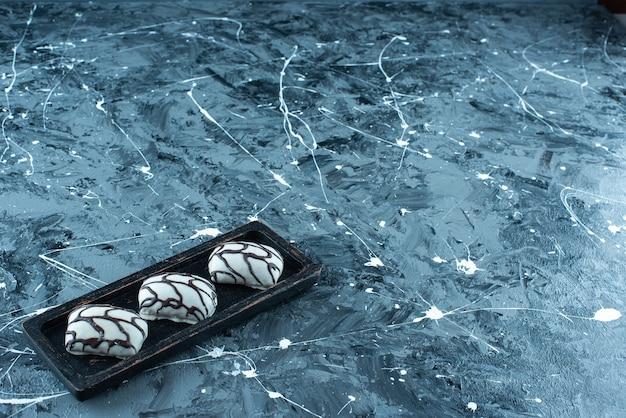 Cukierki na drewnianym talerzu, na niebieskim stole.