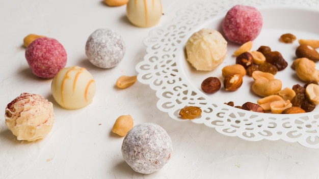 Cukierki obok talerza na białym tle