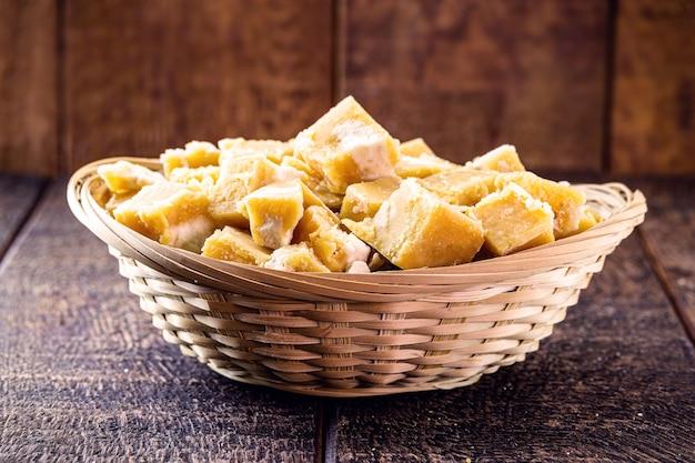 Cukierki rapadura w kawałkach w drewnianej łyżce, cukierki z melasy z trzciny cukrowej
