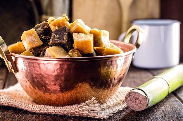 Cukierki rapadura w kawałkach w miedzianym garnku, cukierki z trzciny cukrowej lub melasa z trzciny cukrowej