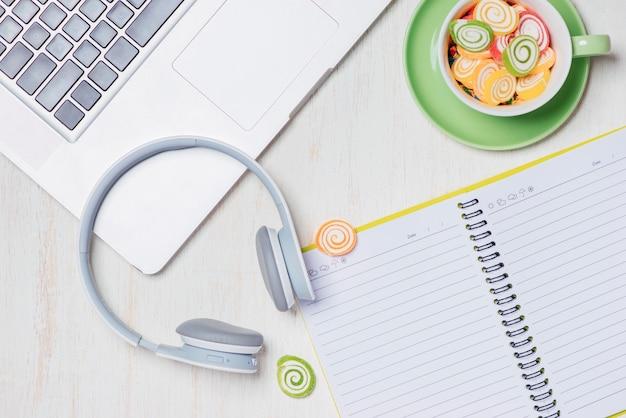 Cukierki, słuchawki i notatnik na drewnianym stole. otwarta przestrzeń do kopiowania.