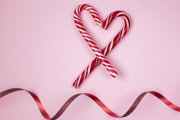 Cukierki świąteczne ze wstążką na różowym tle.