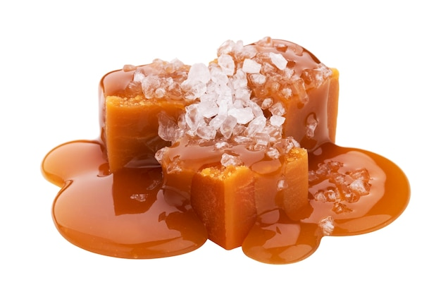 Cukierki toffi z roztopionym sosem karmelowym i solą na białym tle