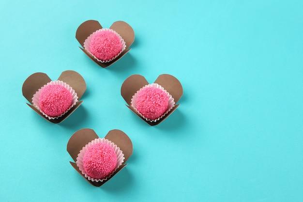 Cukierki truskawkowe tworzące serca na niebieskim tle