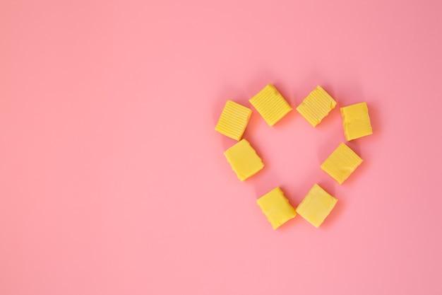 Cukierki ułożone są w kształcie serca na różowym tle.