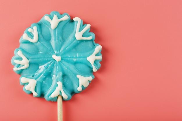 Cukierki w kształcie niebieskiego płatka śniegu na różowym tle. minimalistyczna płaska kompozycja, wolna przestrzeń.