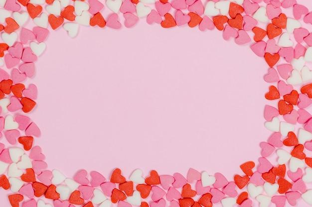 Cukierki w kształcie serca rozrzucone na różowym tle miłość koncepcja ślubu