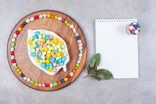 Cukierki w ozdobnym talerzu i dookoła na drewnianej tacy obok notatnika ozdobionego liśćmi na marmurowym tle. wysokiej jakości zdjęcie