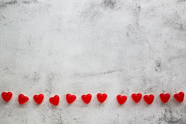 Cukierki walentynki w kształcie serca na szarym tle.