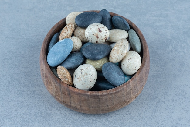 Cukierki z kamienia żwirowego w misce, na marmurowym stole.