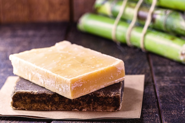 Cukierki z kostki i kawałków brązowego cukru, cukierki z melasy z trzciny cukrowej, na rustykalnym drewnianym stole