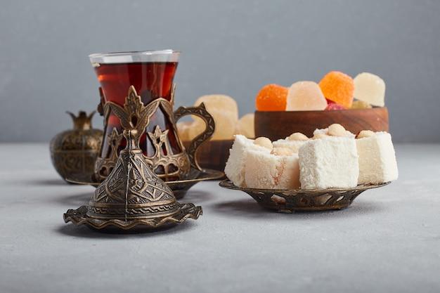 Cukierki żelkowe podawane ze szklanką herbaty.