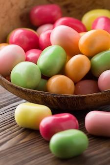 Cukierkowa miska w kolorach pop i drewniana powierzchnia.