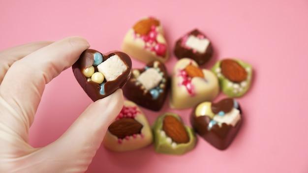 Cukiernicy w rękawiczkach trzymają cukierki w kształcie serca na różowo