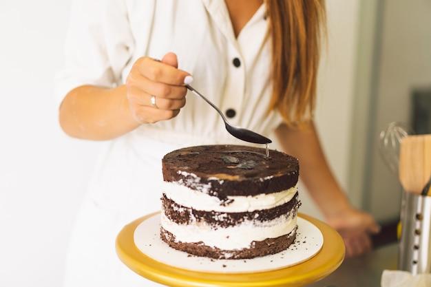 Cukierniczka przygotowuje biszkopt z białą śmietaną i czekoladowymi ciastami do gotowania