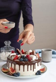 Cukiernik dekorujący białe ciasto z jagodami i czekoladowym ganache nowoczesny pyszny deser