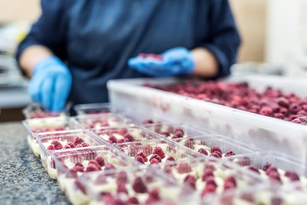 Cukiernik dekorujący wyśmienite desery malinami w fabryce. niesamowite pyszne jedzenie