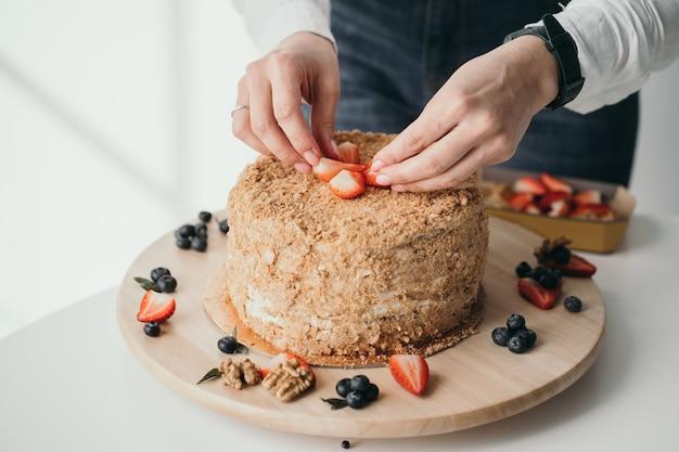 Cukiernik dekoruje ciasto jagodami pyszne ciasto miodowe z jagodami domowa fabryka słodyczy zbliżenie dłoni cukierników