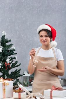 Cukiernik kobieta w kuchennym fartuchu i noworocznym kapeluszu pakuje pyszne prezenty. rama pionowa.