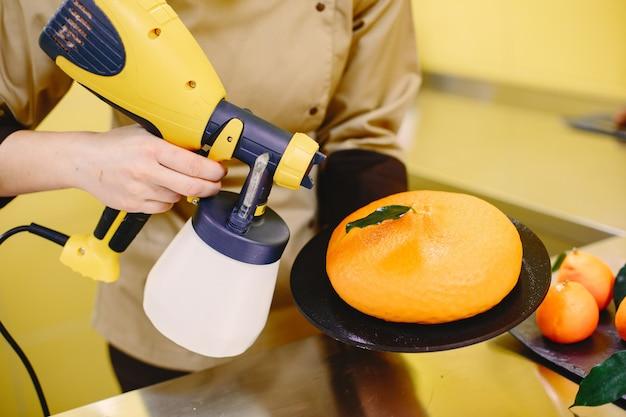 Cukiernik kobieta w tuniki. cukiernik. pani z narzędziami do pieczenia.