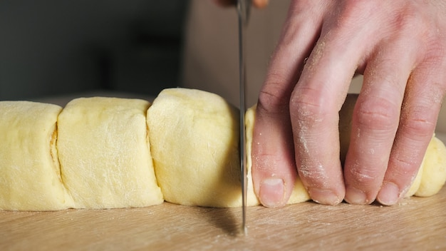Cukiernik kroi bułkę z cynamonem, cukrem i masłem na porcje, aby upiec bułki cynamonowe. zbliżenie dłoni.
