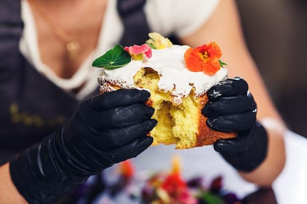 Cukiernik łamie ciasto wielkanocne i pokazuje jego środek.