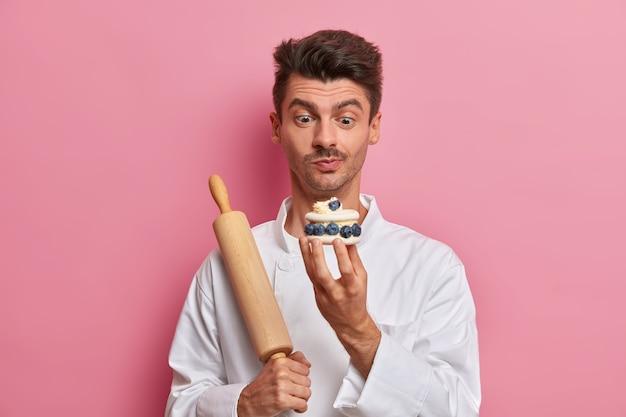 Cukiernik mężczyzna trzyma ręcznie robione pyszne ciasto ozdobione świeżymi jagodami