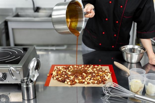 Cukiernik nalewa gorący syrop, karmel na orzechy laskowe, aby zrobić pralinę