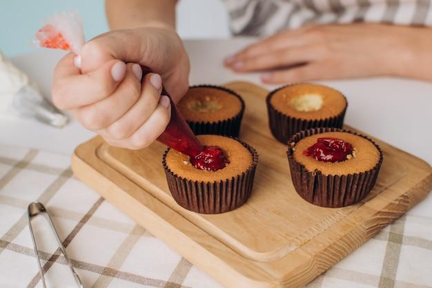 Cukiernik przygotowuje z bliska babeczki. proces pracy szefa kuchni. reklama słodyczy