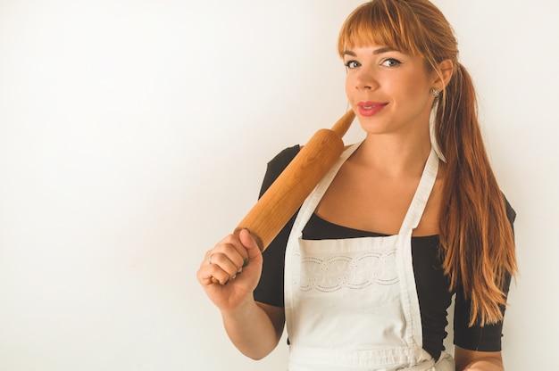 Cukiernik ruda dziewczyna trzyma drewniany wałek do ciasta