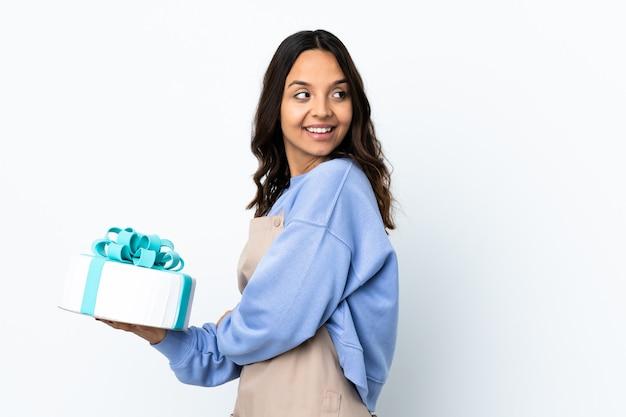 Cukiernik trzyma duży tort na odizolowanej białej ścianie z rękami skrzyżowanymi i szczęśliwy