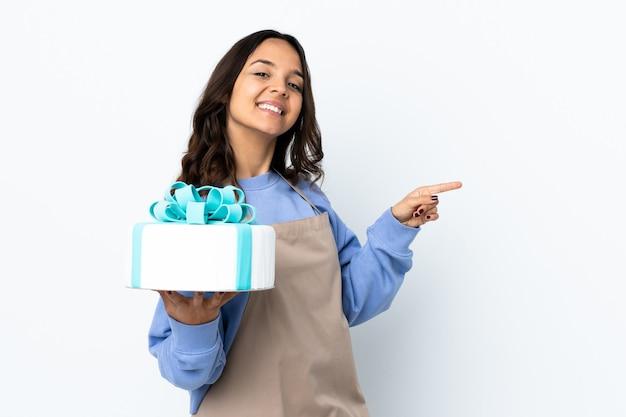 Cukiernik trzyma duży tort na pojedyncze białe palcem wskazującym z boku