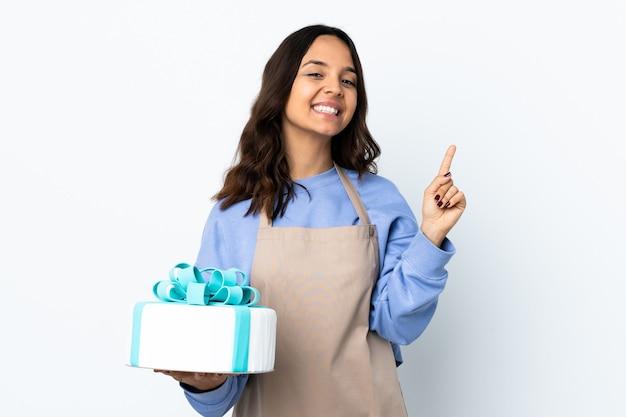 Cukiernik trzyma duży tort nad izolowaną białą ścianą pokazując i podnosząc palec na znak najlepszych
