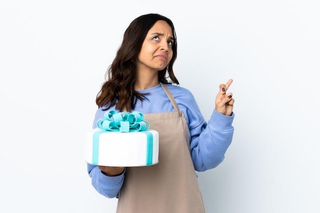Cukiernik trzyma duży tort nad izolowaną białą ścianą ze skrzyżowanymi palcami i życząc wszystkiego najlepszego