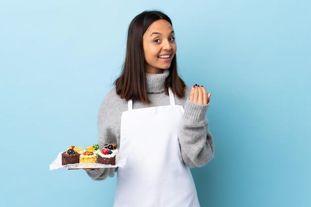 Cukiernik trzyma wielki tort nad izolowaną niebieską ścianą, zapraszając do siebie ręką. cieszę się, że przyszedłeś