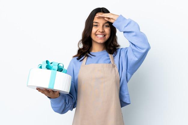 Cukiernik trzymający duże ciasto na białym tle pozdrawiając ręką ze szczęśliwym wyrazem twarzy
