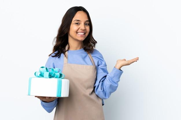 Cukiernik trzymający duże ciasto na białym tle, trzymający wyimaginowaną copyspace na dłoni, aby wstawić reklamę