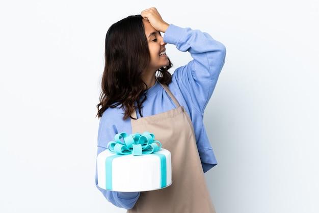 Cukiernik trzymający duży tort na białym tle coś sobie uświadomił i zamierza znaleźć rozwiązanie