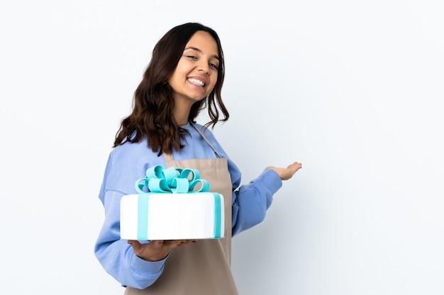 Cukiernik trzymający duży tort na odizolowanej białej ścianie wyciągając ręce na bok, by zaprosić do przyjścia