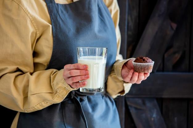 Cukiernik w fartuchu trzyma ciasto czekoladowe i mleko