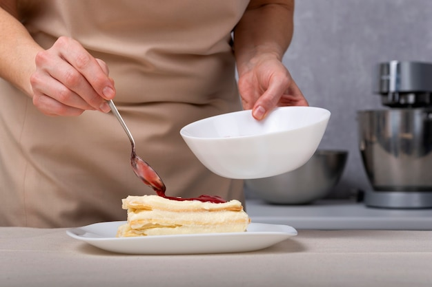 Cukiernik w trakcie robienia ciasta z dżemem jagodowym. ręce cukiernika.