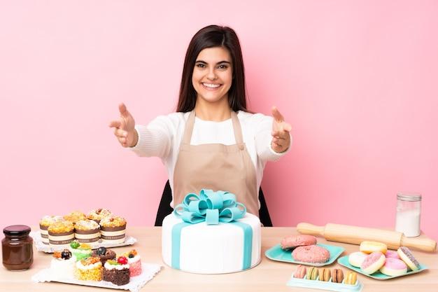 Cukiernik z dużym ciastem na stole nad izolowaną różową ścianą, przedstawiając i zapraszając do pomocy