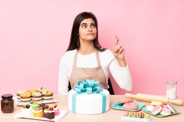 Cukiernik z dużym ciastem na stole nad izolowaną różową ścianą ze skrzyżowanymi palcami i życzeniem wszystkiego najlepszego