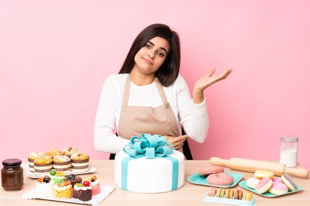 Cukiernik z dużym ciastem na stole nad izolowanym różem niezadowolony, że czegoś nie rozumie