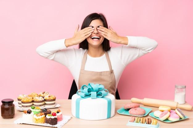 Cukiernik z dużym ciastem w stole nad różową ścianą zasłaniającą oczy rękoma