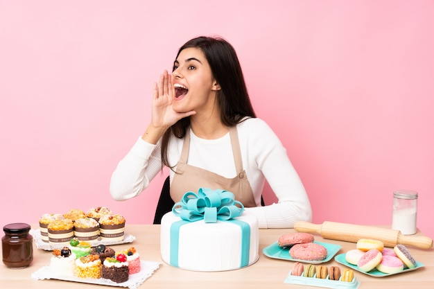Cukiernik z wielkim ciastem w stole nad odizolowaną różową ścianą krzyczącą z szeroko otwartymi ustami do boku